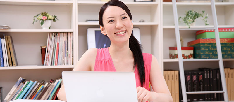 女性が笑顔で生き生きと仕事をしている画像