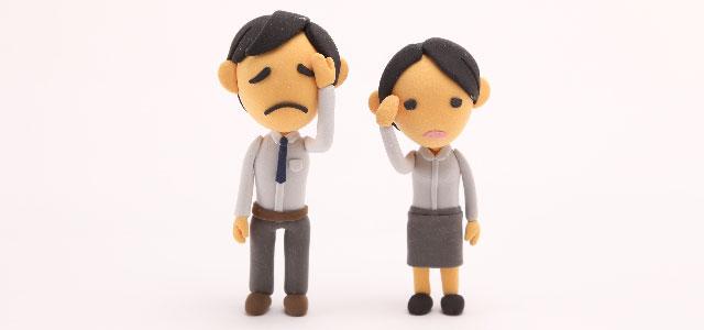広告業は身体が資本!でもたまには病気してしまった男性と女性の人形が並んで額をおさえている画像。